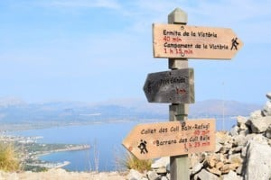 Hiking trail signs and Pollensa Bay near Alcudia on Mallorca